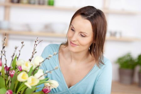 Smiling woman is looking at a bouquet of flowers