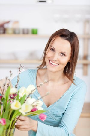 Smiling woman is tending to her bouquet of flowers