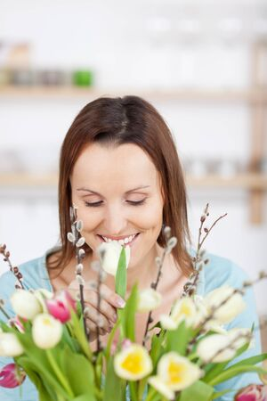 Pretty woman is smiling while arranging flowers photo