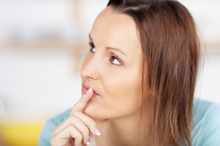 forgetful: A pensive young woman looking up, finger on lips