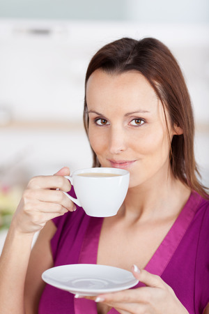 contentment: Attractive woman standing enjoying a cup of coffee during a coffee break and looking at the camera with an expression of contentment Stock Photo