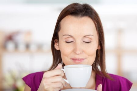 stimulate: Woman savouring the aroma of coffee standing smelling the coffee in her cup and closing her eyes in appreciation