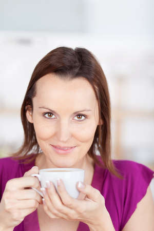 cradling: Attractive young woman enjoying her coffee cradling the cup in her hands and smiling at the camera Stock Photo