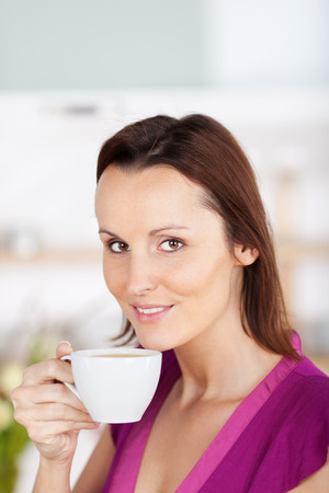addictive drinking: Smiling woman with a cup of tea or coffee