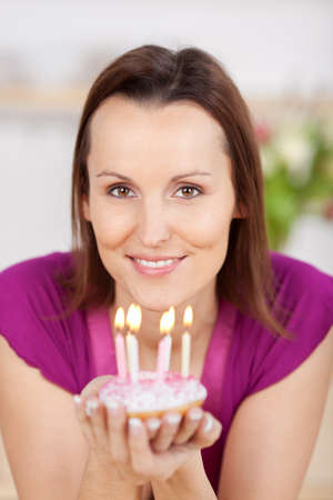 merrymaking: Attractive woman with a small birthday cake decorated with icing and sprinkles and topped with burning candles cupped in her hands