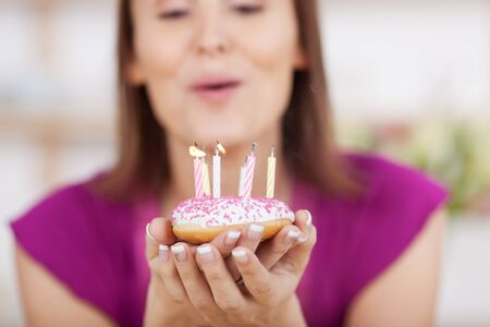 Woman blowing out her birthday candles on a cake iced small cupped in her hands, shallow dof