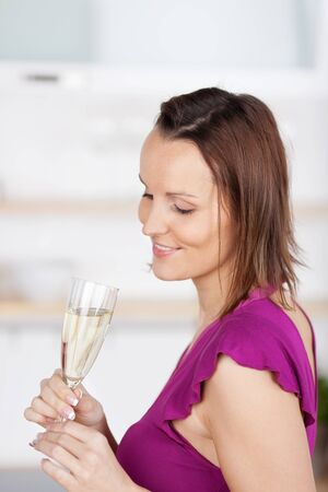 yearning: Woman with a flute of champagne standing looking at the glass with a look of gentle yearning as she stands daydreaming and celebrating a special event