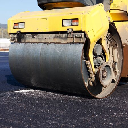 resurfacing: Roller doing roadworks flattening and compacting newly laid tar during resurfacing