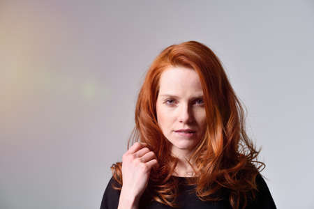 red haired: Close up Angry Red Haired Young Woman with Closed Fist Looking at the Camera, Isolated on Gray Background