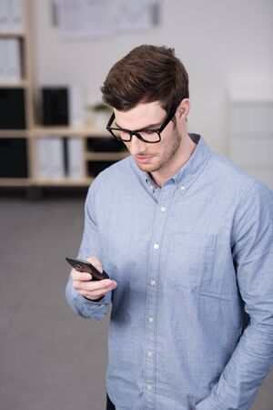 his shirt sleeves: Close up Handsome Young Man, Wearing Long Sleeves Shirt with Eyeglasses, Busy at his Mobile Phone.
