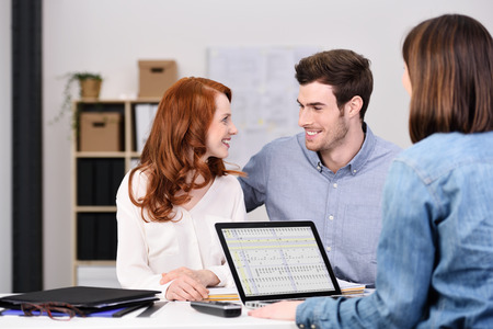 Happy Business Couple Looking Each Other While Having a Discussion to a Businesswoman with Laptop Computer