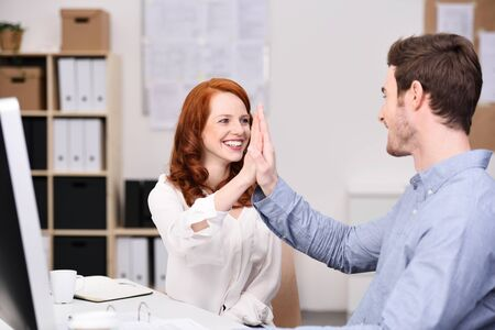 2 5: Successful young business team celebrating and giving a high fives as they laugh and smile, man and woman in an office Stock Photo