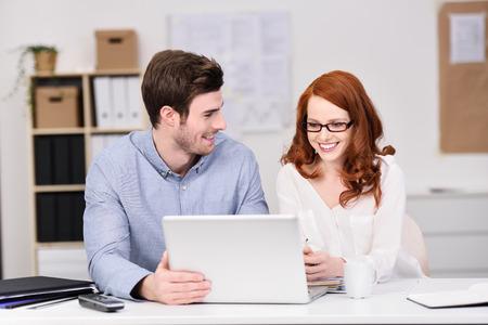 jornada de trabajo: Equipo de negocios joven Satisfecho trabajando juntos en un ordenador port�til sonriente al ver su proyecto viene a buen t�rmino, el hombre y la mujer Foto de archivo
