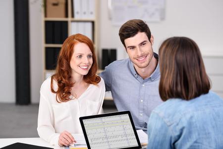 Cierre de Feliz Pareja joven escuchar un Empresaria Hablando de planes en la mesa de trabajo dentro de la oficina.
