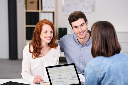 advice: Close up Happy Young Couple Listening to a Businesswoman Talking About Plans at the Worktable Inside the Office. Stock Photo
