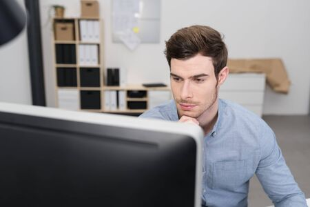 glum: Serious young businessman reading his computer screen with a glum expression and his chin resting on his hand, view over the top of the monitor
