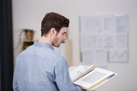 palm reading: Young man standing doing research in the office reading from a hardcover book balanced on his palm, view over his shoulder from the rear