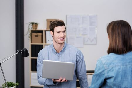 chats: Handsome young businessman smiling as he chats to a female colleague while balancing his laptop computer on his arm Stock Photo