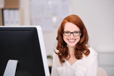 redhaired: Friendly confident young businesswoman with shoulder length red hair wearing glasses looking at the camera with a beaming happy smile