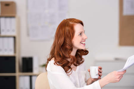redhaired: Pretty young redhead businesswoman drinking coffee turning to hand over a paper document with a smile Stock Photo