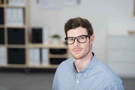 scholarly: Serious scholarly young businessman wearing nerdy dark framed glasses looking directly at the camera, with copyspace
