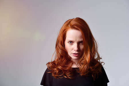 glowering: Angry young woman with pretty shoulder length red hair standing glowering at the camera with a serious expression, on grey with copyspace Stock Photo