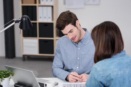 traineeship: Close up Good Looking Businessman Discussing with Female Co-Worker at his Office About the Document on the Table. Stock Photo
