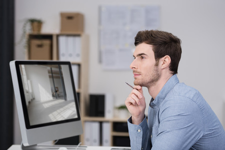 Close up Thoughtful Young Businessman Sitting at his Desk with Computer Looking to the Left of the Frame with Hand on his Chin. photo