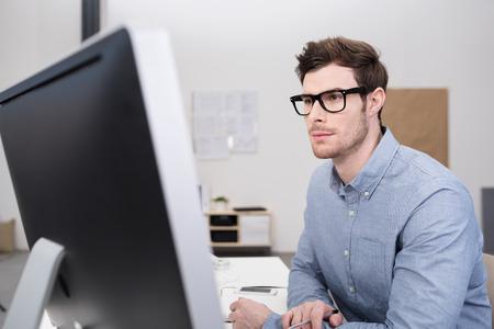 puesto de trabajo: Cierre de negocios joven serio con las lentes Sentado en su mesa de trabajo dentro de la oficina y frente a un monitor de ordenador