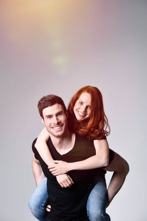 red hair woman: Close up Handsome Man Carrying his Pretty Girl on his Back While Smiling at the Camera. Captured in Studio with Gray Background.