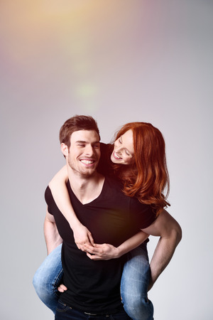 sweethearts: Portrait of a Happy Sweethearts - Young Handsome Man Carrying his Girlfriend on his Back at the Studio with Gray Background.
