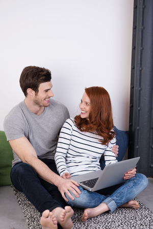 Happy Young White Couple with Laptop Computer, Sitting on the Floor at the Living Room with Cloth, Looking Each Other photo