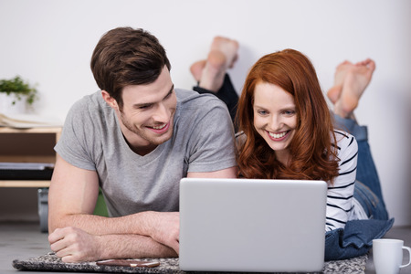 catch up: Barefoot happy couple relaxing at home lying on the floor with a laptop smiling as they catch up on their social media