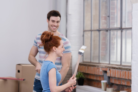unconventionally: Amused young man smiling at his wife as she brandishes a paintbrush full of paint as they work together renovating their apartment Stock Photo