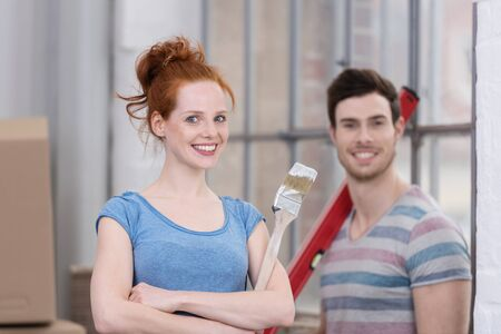 proud: Smiling happy couple renovating their house standing smiling at the camera with paint brushes and tools in their hands, focus to the woman