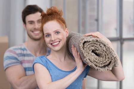 redecorate: Happy friendly young woman carrying a new neutral colored carpet with her husband as they redecorate their new home