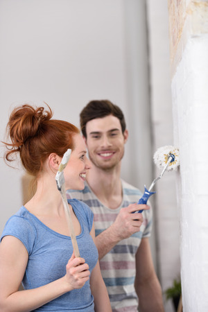 domiciles: Happy affectionate young couple renovating their home standing smiling at each other as they paint a white wall