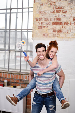 redecorating: Playful fun loving young couple enjoying a piggy back ride while redecorating their new house