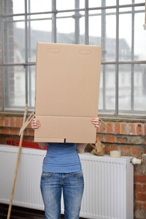 mischievous: Mischievous young woman hiding in a brown cardboard box over her head as she moves to her new home Stock Photo