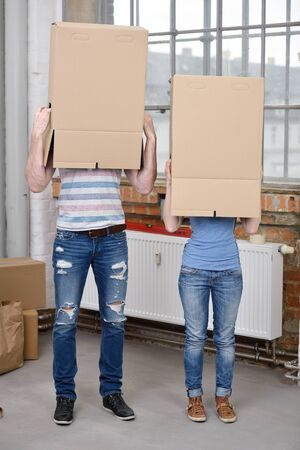head home: Young couple standing side by side in their casual jeans with brown cardboard boxes over their heads while moving house, blank surface for your text