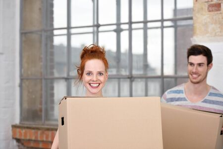 moving box: Excited attractive young redhead woman moving house beaming happily as she carries a cardboard box watched by her husband