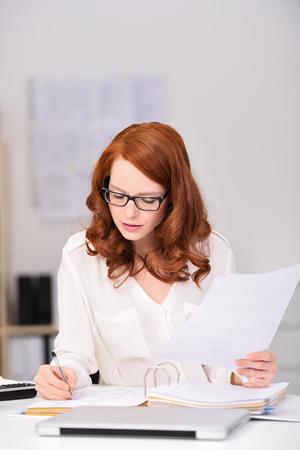 persona escribiendo: Cierre de la oficina ocupada joven mujer sentada en su mesa de trabajo, Escribir Documento serio mientras que sostiene otros papeles. Foto de archivo