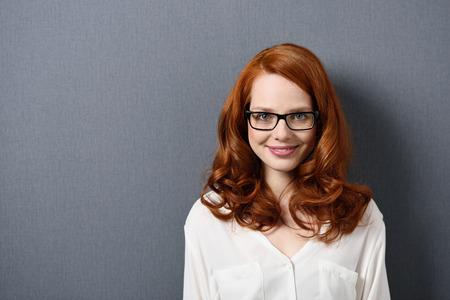 red hair woman: Close up Smiling Young Woman with Brown Wavy Hair Wearing Eyeglasses on a Gray Background, Emphasizing Copy Space.