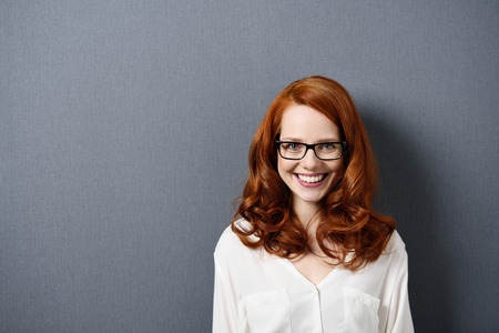 emphasizing: Happy Young Woman in White Shirt with Eyeglasses Standing on a Gray Wall Background, Emphasizing Copy Space.