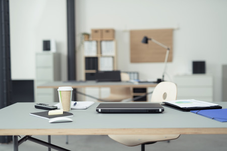 事務用品, ラップトップ コンピューター、携帯電話上にコーヒーのカップと実業家のオフィスのテーブル。 写真素材