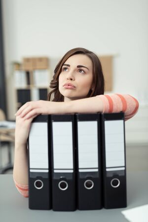 contemplative: Young businesswoman standing thinking resting her arm across a row of office binders with blank labels as the stares in to the air with a contemplative expression Stock Photo