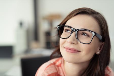 mujeres trabajando: Mujer joven sonriente llevaba anteojos con marcos y Negro Mirar hacia arriba, como si soñar despierto o pensando en algo feliz