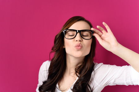puckering lips: Young Brunette Woman Wearing Eyeglasses with Black Frames Puckering Lips with Eyes Closed, Blowing Kiss Towards Camera Stock Photo