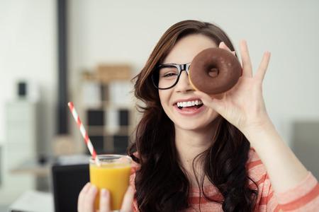 Lachende jonge vrouw met een verse lekkere chocolade donut op haar ogen over haar bril terwijl een glas jus d'orange in haar andere hand