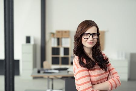 Zblízka jistý atraktivní mladá žena na sobě Stripe tričko a brýle, usmívala se na kameru s rukama přejezdu před jejím těle.